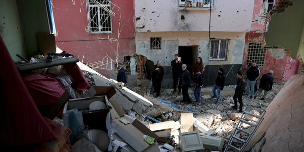 People look at buildings which were damaged during the security operations and clashes between Turkish security forces and Kurdish militants, in Sur district of Diyarbakir, Turkey